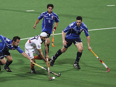 India's Chandi fights for the ball with Italy's Murgia and his teammate Cottam during their London 2012 Olympic Games men's field hockey qualifying match in New Delhi. Reuters