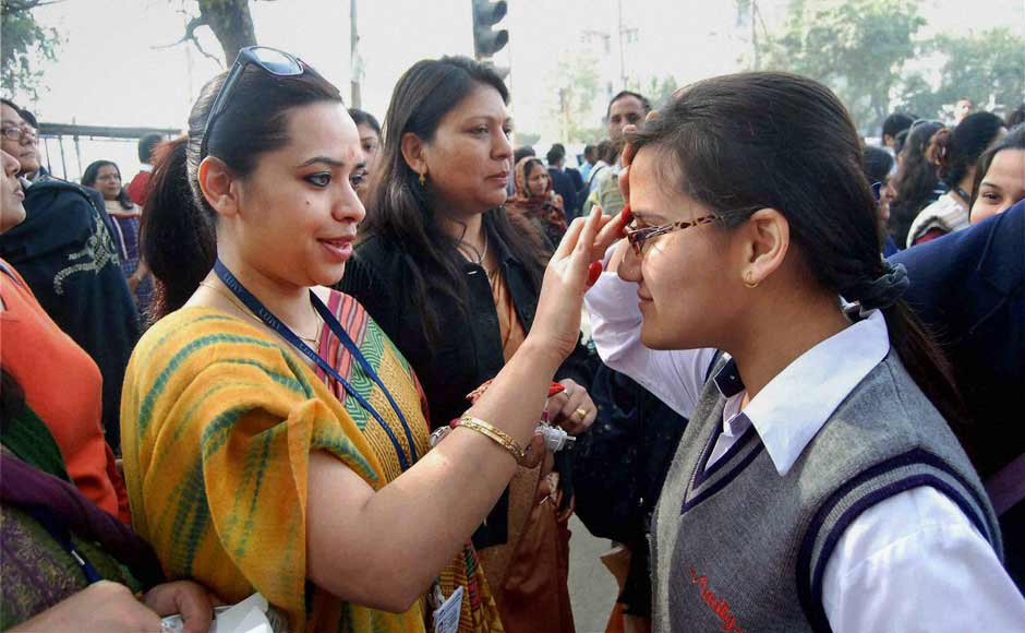 Teachers wishing good luck to students at an examination centre before they appear in their 10th standard exams of CBSE in Noida on Thursday. PTI