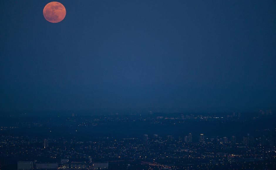 The supermoon is seen rising over Vancouver, British Columbia. AP