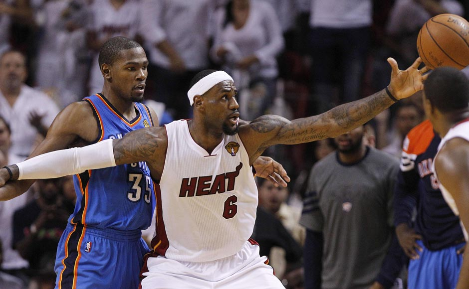 Miami Heat small forward LeBron James (6) reels in the ball as Oklahoma City Thunder small forward Kevin Durant (35) defends during the second half at Game 4 of the NBA Finals basketball series. AP