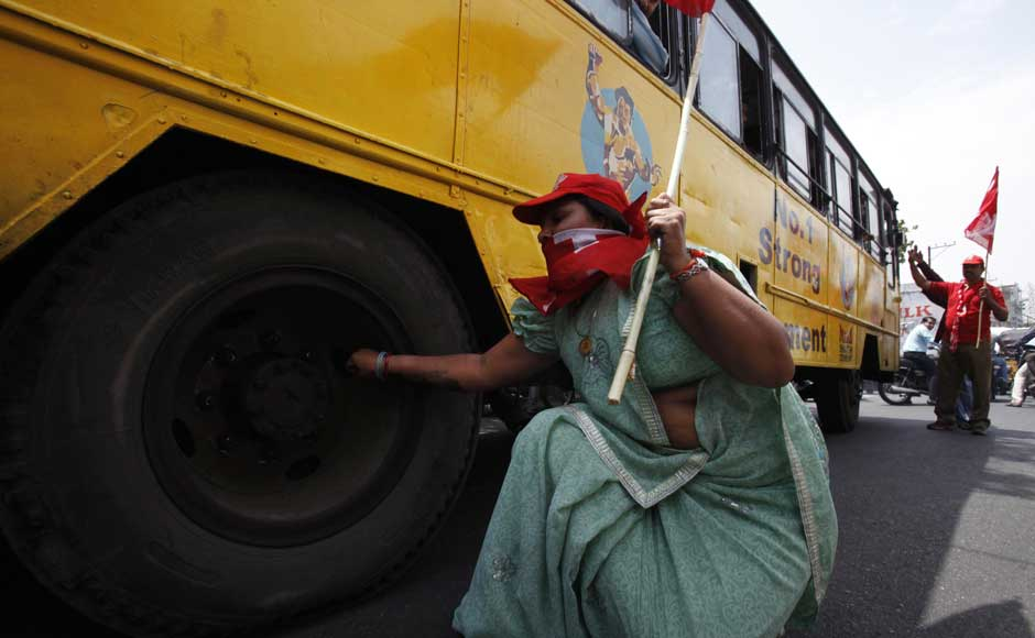 How dare they run buses while I'm striking, let's puncture the damn tyres: A left party activist deflates a tire of a bus during a nationwide strike against a steep hike in gas prices in Hyderabad. Mahesh Kumar A/ AP