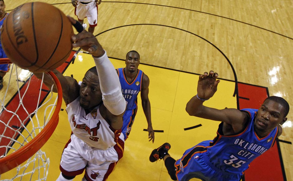 Miami Heat shooting guard Dwyane Wade (3) gets past Oklahoma City Thunder small forward Kevin Durant (35) and power forward Serge Ibaka (9) from Republic of Congo to dunk the ball during the second half at Game 3 of the NBA finals basketball series. AP