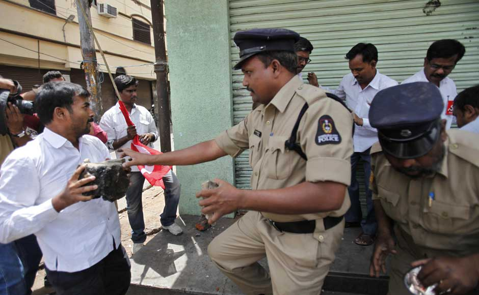 Ok I'm not really angry, I just want to use this bandh as an excuse to get my hands on some booze: Policemen stop activists of left parties who tried to attack a wine shop which was open during a nationwide strike against a steep hike in gas prices in Hyderabad. Mahesh Kumar A/AP