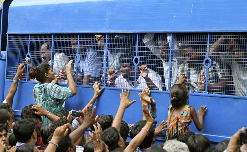 Relatives crowd around a police vehicle carrying convicts after a special court in Ahmedabad found them guilty of 2002 Naroda Patiya massacre on 29 August.AP