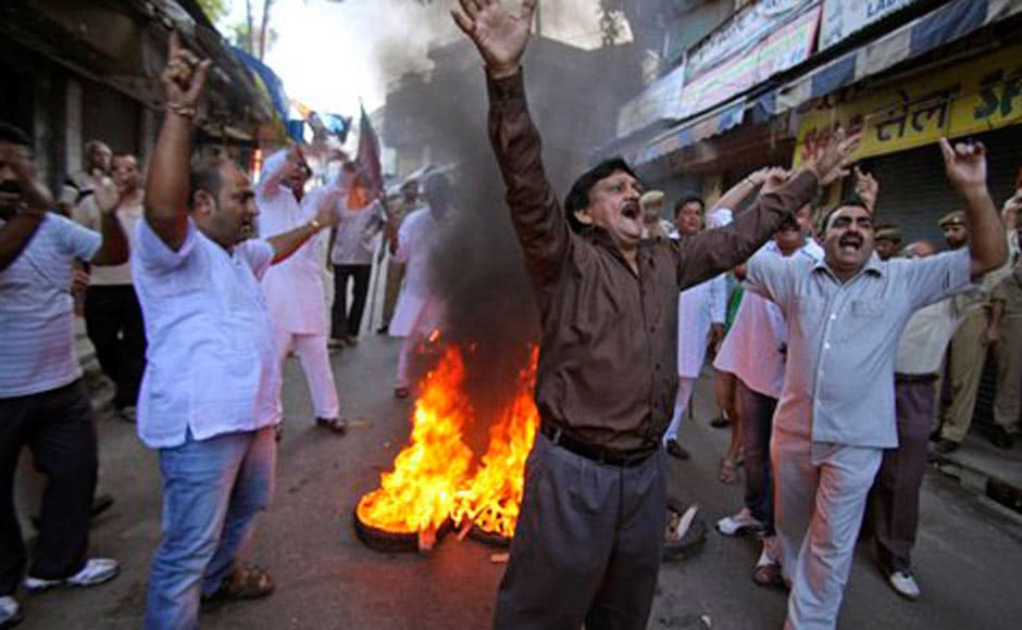 BJP activists shout slogans as they burn tires during a nationwide strike in Jammu. AP