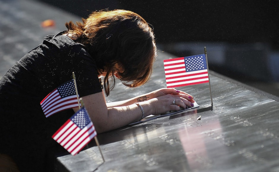 Melissa Pullis, of Hazlet, New Jersey, pauses at the engraving for her husband Edward during ceremonies marking the 11th anniversary of the 9/11 attacks on the World Trade Center in New York, September 11, 2012. Reuters
