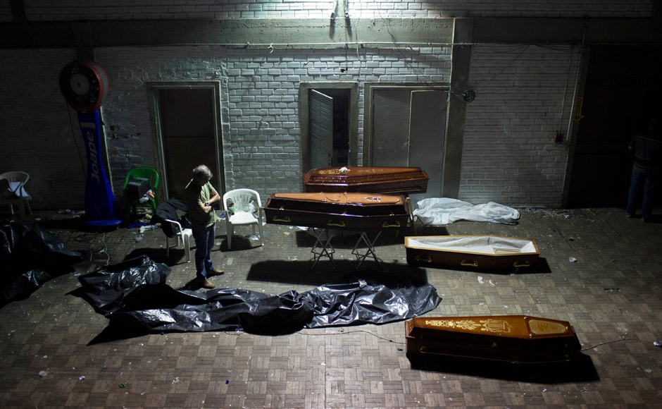 A man stands around coffins containing the remains of victims after the bodies were identified at a gymnasium in Santa Maria city, Rio Grande do Sul state, Brazil, Sunday, Jan 27, 2013.AP