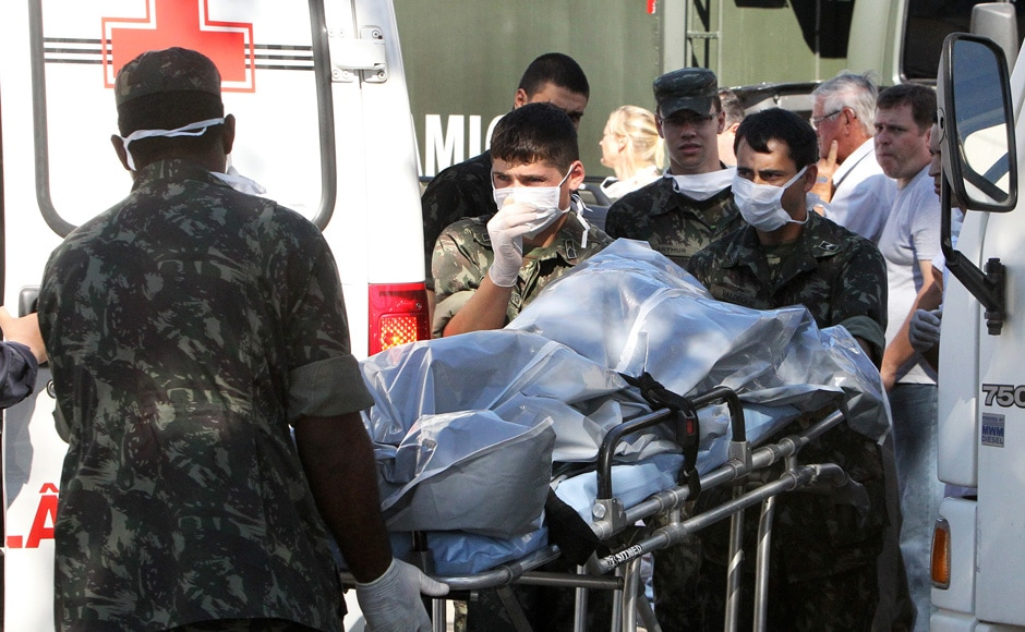 Brazil's soldiers carry the remains of a victim outside a gymnasium where bodies were brought for identification in Santa Maria city, Rio Grande do Sul state, Brazil, Sunday, Jan 27, 2013. AP