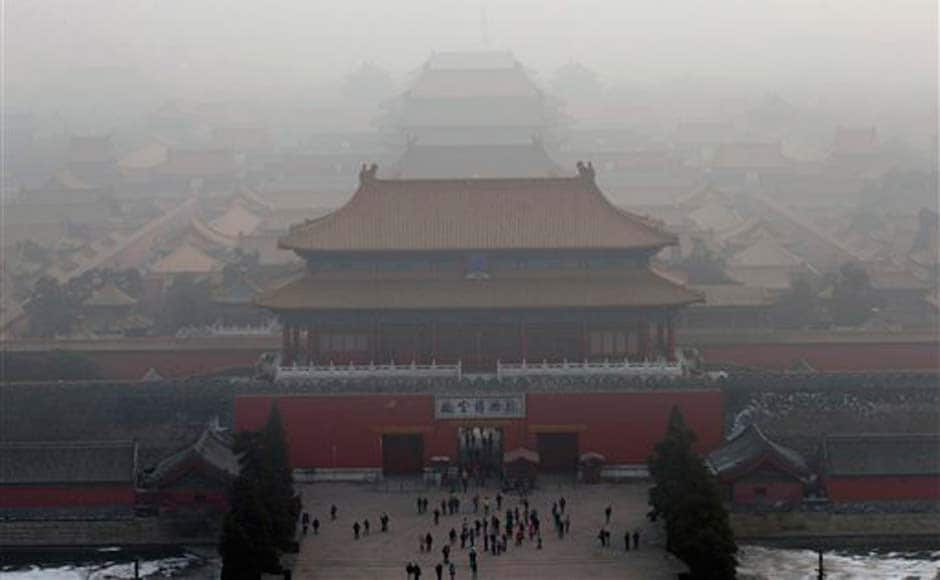 Visitors gather near an entrance to the Forbidden city amid the haze in Beijing : AP