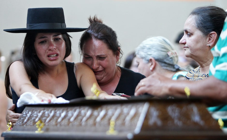 Relatives cry next to a coffin at a gymnasium where bodies were brought for identification in Santa Maria city, Rio Grande do Sul state, Brazil, Sunday, Jan 27, 2013. AP