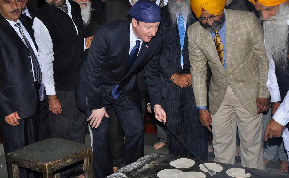 UK PM David Cameron prepares bread at a community kitchen during his visit to the holy Sikh shrine of Golden temple. Reuters