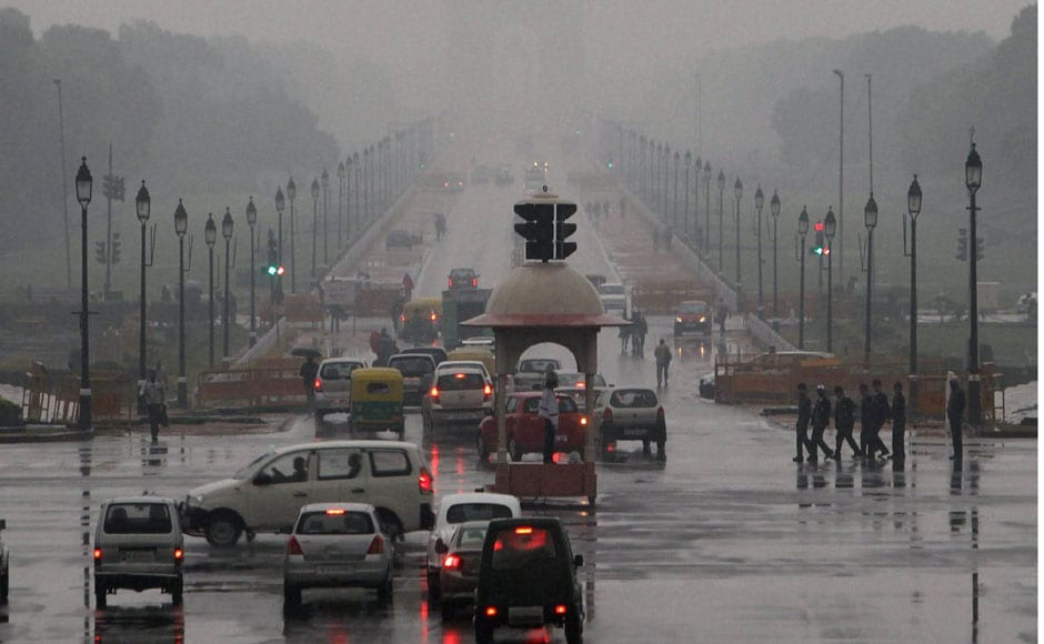 Vehicles seen plying at New Delhi's Vijay Chowk on a very cloudy morning. PTI