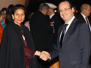 French President Francois Hollande (R) is greeted by Minister of State for External Affairs Preneet Kaur on his arrival at the airport, in New Delhi. PTI