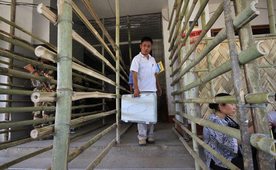 A polling officer walks with an Electronic Voting Machine before leaving for his deputed polling station in Dimapur. AP