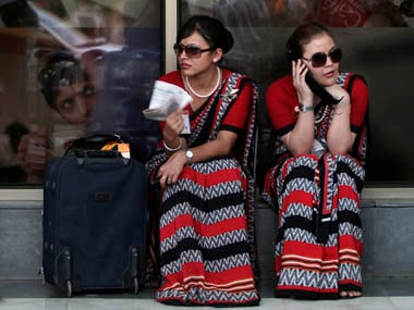 Air India air hostesses sit outside the domestic airport in New Delhi