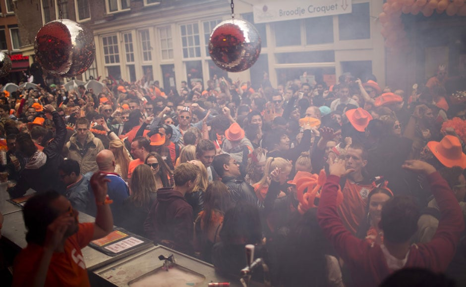People dance on the streets of Amsterdam, wearing orange hats, in celebration of their new king. AP