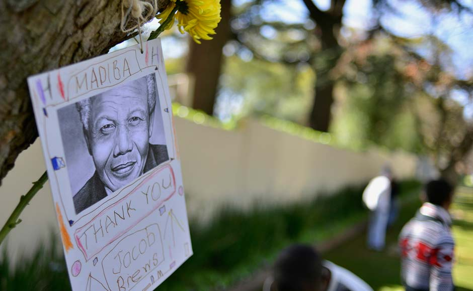 A message of support hangs from a tree outside the home of former President Nelson Mandela in Houghton, Johannesburg: Reuters