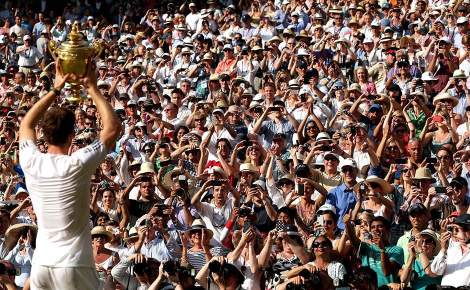 Fans cheer and take photographs as Andy Murray of Great Britain poses with the Gentlemen's Singles Trophy following his victory in the Gentlemen's Singles Final match against Novak Djokovic at Wimbledon. Clive Brunskill/Getty Images