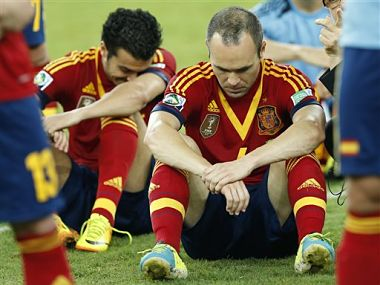 Spain's Andres Iniesta, center, and Pedro Rodriguez, left, sit dejected on the pitch after losing the  Confederations Cup final. AP