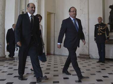 Head of the Syrian National Coalition, Ahmad al-Jarba, left, and France's President Francois Hollande walk in the lobby of the Elysee Palace. AP