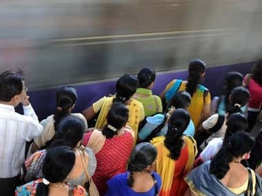 Female commuters wait to board a train at one of Mumbai's railway stations. AFP