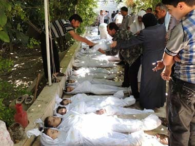 This citizen journalism image provided by the Local Committee of Arbeen which has been authenticated based on its contents and other AP reporting, shows Syrian citizens trying to identify dead bodies, after an alleged poisonous gas attack fired by regime forces. AP