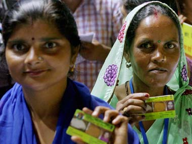 Women show their Food Security card after the scheme was launched in Delhi. PTI