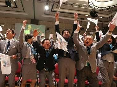 Japan's Prime Minister Shinzo Abe, fourth from left, and Tokyo's Governor Naoki Inose, third from left, celebrate with other members of the Tokyo delegation. AP