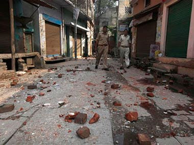 Indian policemen walk on a road scattered with bricks and stones thrown during a communal clash in Muzaffarnagar, about 125 kilometers (78 miles) north of New Delhi, India, Monday, Sept. 9, 2013. Sectarian violence was spreading into new areas of northern India on Monday, despite an army-enforced curfew put in place after deadly weekend clashes broke out between Hindus and Muslims that has killed at least 28 people and left many more missing. AP
