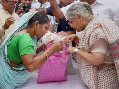 Delhi CM Sheila Dikshit distributes subsidised food grain in New Delhi. PTI
