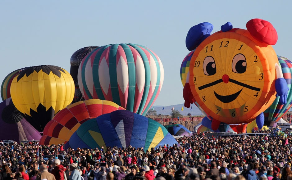 Hot air balloons, one of them shaped like a clock, are prepared before taking flight during the 42nd annual Albuquerque International Balloon Fiesta in Albuquerque, New Mexico. Thousands of spectators gathered on Saturday at the city's balloon park to watch more than 500 balloons of all shapes and sizes lift off in two stages during the so-called mass ascensions: Reuters
