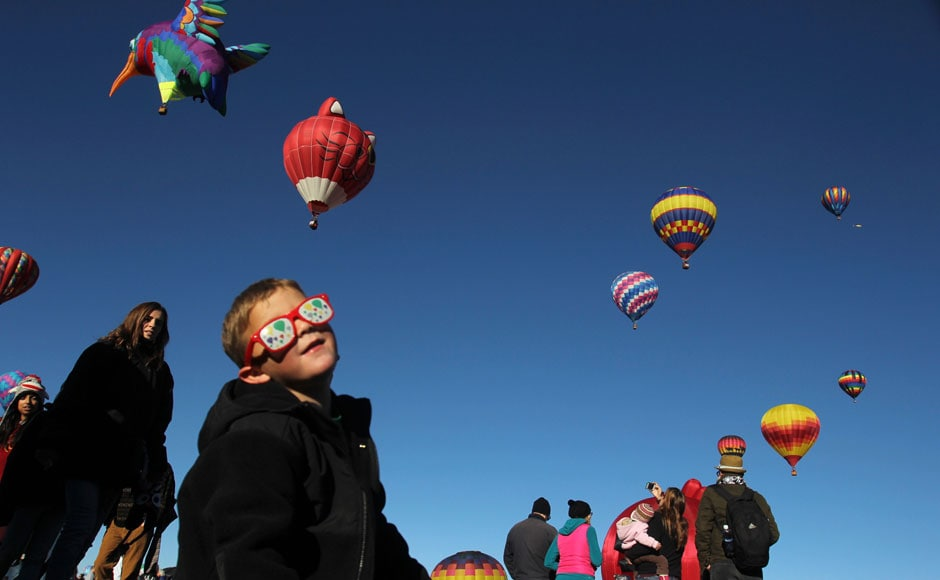Balloons in their eyes: A little boy enthralled as more than 500 balloons of all shapes and sizes lift off in two stages: Reuters