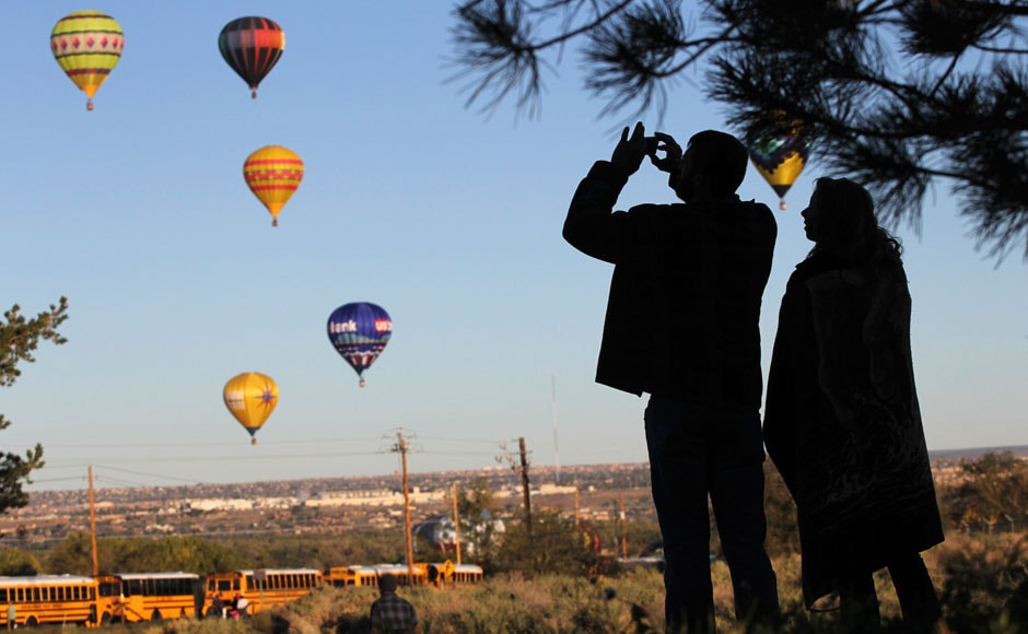 A visitor takes pictures of hot air balloons flying overhead: Reuters