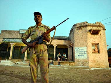 A security official stands guard outside a polling both in Madhya Pradesh. PTI