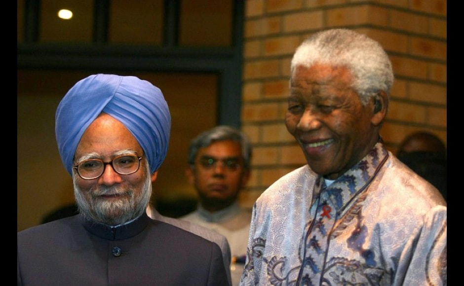 Indian Prime Minister Manmohan Singh (L) and former South African President and anti-apartheid activist Nelson Mandela (C) arrive at the Nelson Madela Foundation in Johannesburg, 02 0ctober 2006. Singh's four-day visit starting last Saturday focuses on beefing up trade between the two regional powerhouses from four billion dollars last year, according to Indian figures, to three times that by the end of the decade. AFP