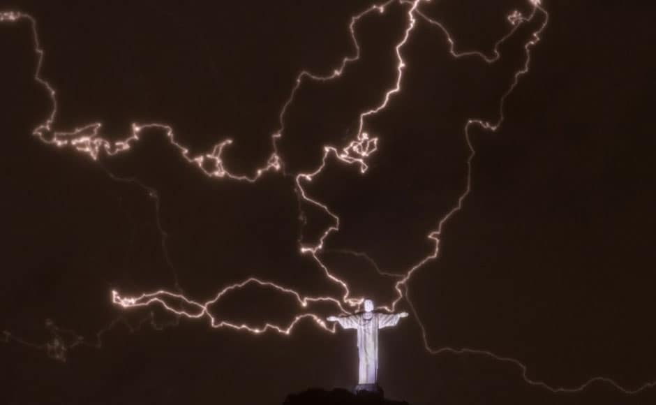 A lightning flashes over the statue of Christ the Redeemer on top of the Corcovado hill in Rio de Janeiro, Brazil, on January 16, 2014.  AFP