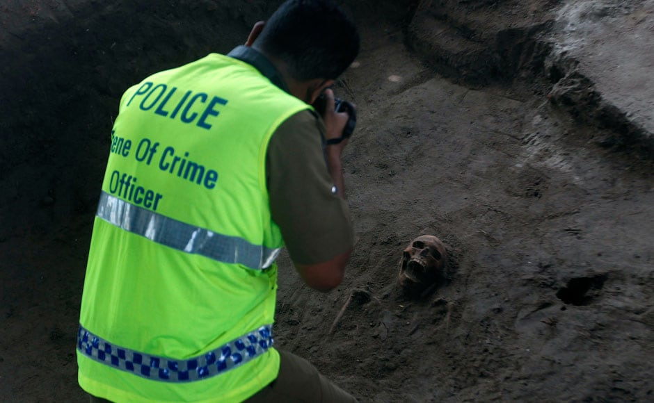 A police officer takes a picture of a human skull at a construction site in the former war zone in Mannar, about 327 km (203 miles) from the capital Colombo. Reuters
