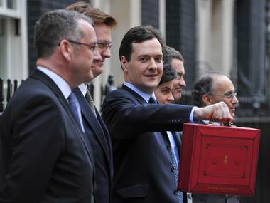 Britain's Chancellor of the Exchequer George Osborne, holds his budget case for the cameras as he stands with members of his Treasury team outside number 11 Downing Street