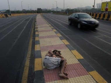 A homeless man sleeps on a road divider in Delhi. AFP