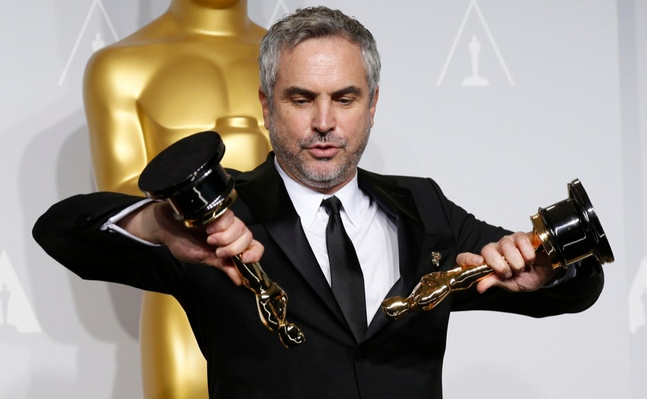 "Alfonso Cuaron poses with the awards for best director and best film editing for ""Gravity"" at the 86th Academy Awards in Hollywood, California March 2, 2014.  REUTERS"