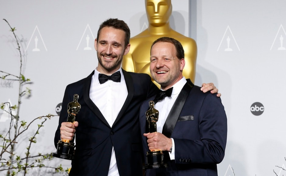 "Anders Walter and Kim Magnusson (R) hold their Oscars for the best live action short film winners for ""Helium"" at the 86th Academy Awards in Hollywood, California March 2, 2014.  REUTERS"