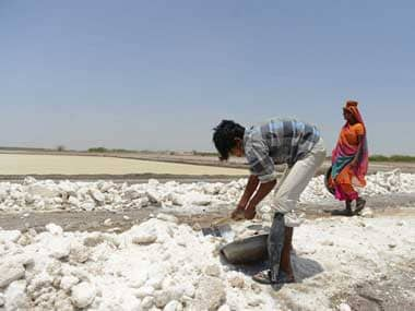 Salt pan workers salvage thick pieces of the mineral, ruined by rains, from a flooded salt pan near Odu village in the Little Rann of Kutch region, some 150 km from Ahmedabad. AFP