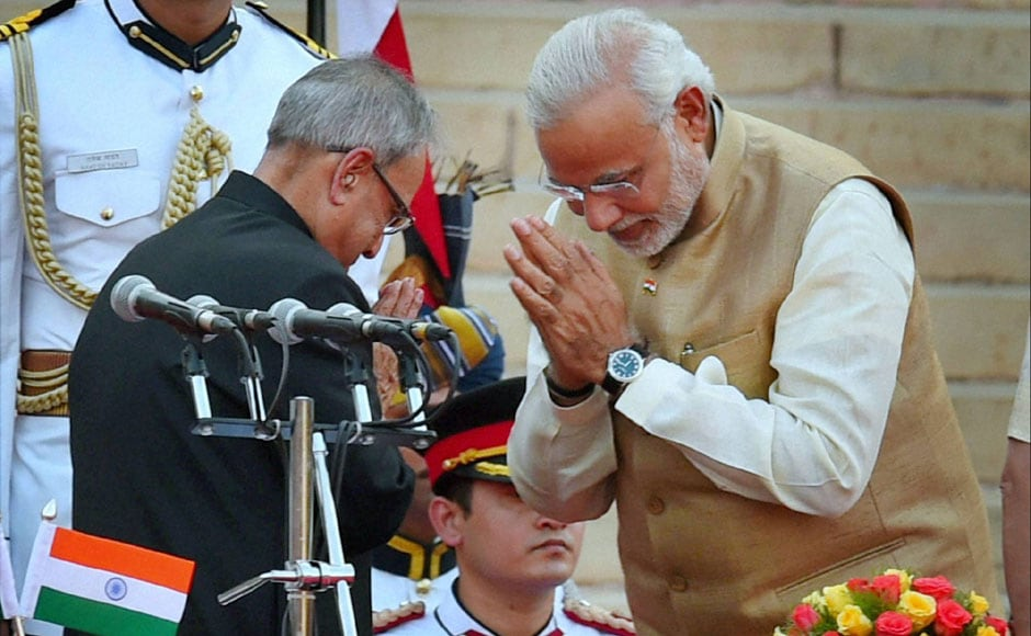 Narendra Modi greets President Pranab Mukherjee during his swearing-in ceremony. PTI