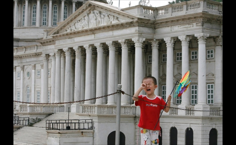 Boy cries near a replica of the United States Capitol building at Beijing World Park