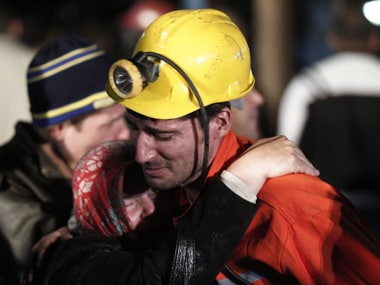A rescued miner hugs a relative in front of the coal mine site in Soma. Reuters