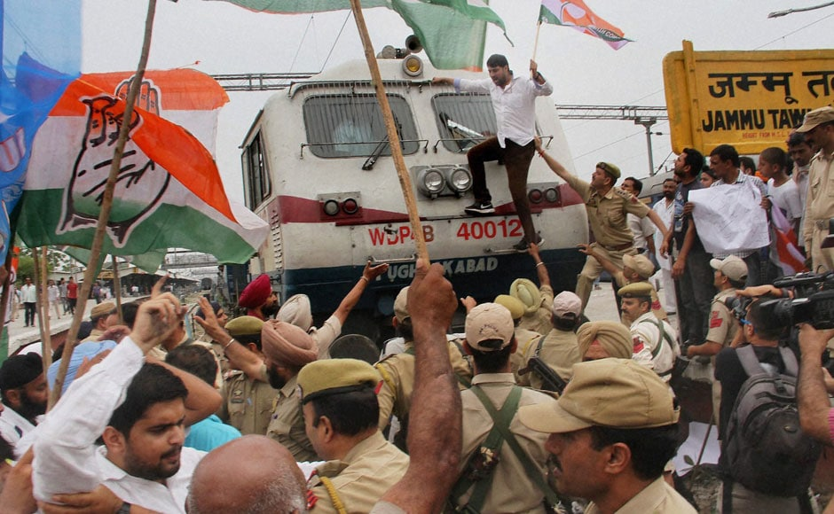 Congress and NSUI activists  block a train in protest against hike in railway fares, at Jammu railway station on Wednesday. PTI