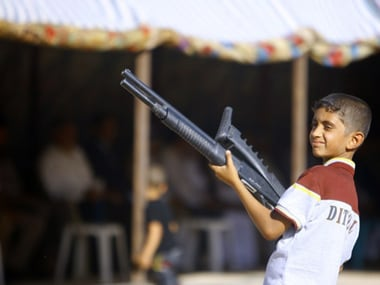 An Iraqi boy holds a weapon as he takes part in a gathering of Shiite tribesman. AFP image