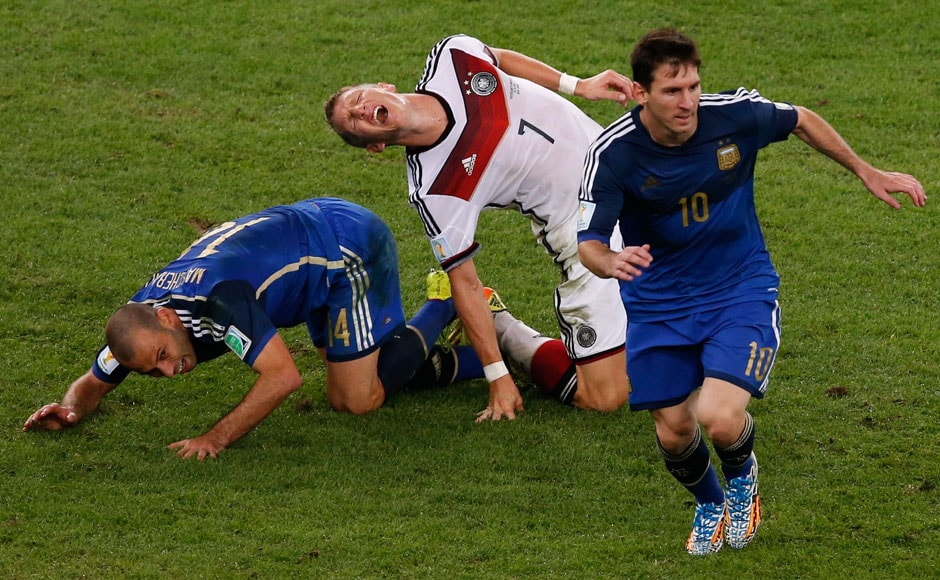 Germany's Bastian Schweinsteiger reacts as he falls on the pitch past Argentina's Javier Mascherano (R) and Lionel Messi (R) during extra time in their 2014 World Cup final at the Maracana stadium in Rio de Janeiro July 13, 2014.  REUTERS