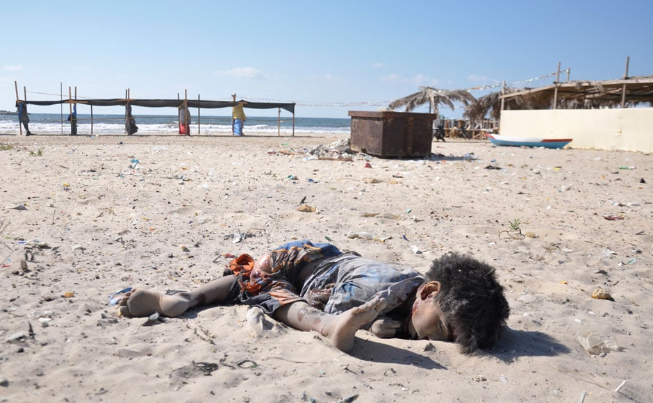 The body of a boy, whom medics said was killed by a shell fired by an Israeli naval gunboat, is seen on a beach in Gaza City July 16, 2014. Four Palestinian children were killed and one was critically wounded on the Gaza beach on Wednesday by the shell fired by the Israeli naval gunboat, a Palestinian health official said. Asked about the incident, an Israeli military spokesman in Tel Aviv said he was checking the report. Gaza health officials said 207 Palestinians, most of them civilians, had been killed in air and naval barrages, in the worst flareup of Israeli-Palestinian violence in two years. One Israeli has been killed by shelling from Gaza that has made a race to shelter a daily routine for hundreds of thousands in Israel.  REUTERS