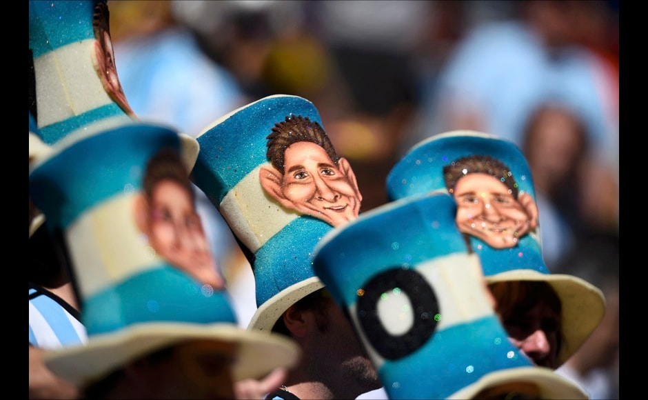 Fans wearing hats decorated with a caricature of Argentina's Lionel Messi wait for the start of the 2014 World Cup quarter-finals between Argentina and Belgium at the Brasilia national stadium in Brasilia July 5, 2014. REUTERS